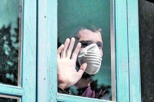 hombre con cubrebocas en ventana